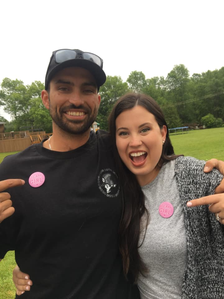 """Gender Reveal Party - mom and dad pointing to """"Team Girl"""" badges on shirts."""
