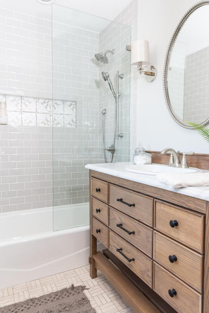 Best Bathrooms by Joanna Gaines; Fixer upper's top bathroom renovations by Joanna and chip Gaines! These rustic, country with hints of modern perfection bathrooms are everything #joannagaines #bathroom #bathrooms #renovations || Gray Tile, Grey subway tile, wood vanity, round mirror - Nikki's Plate