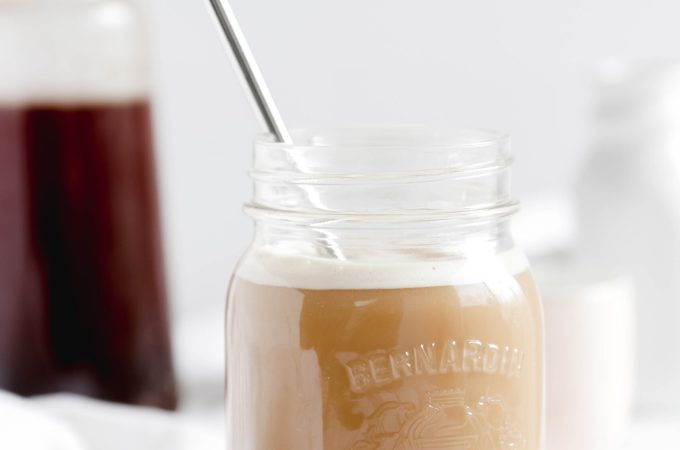 Overnight Cinnamon Cold Brew Coffee - mason jar full of cold coffee beverage with stainless steel straw over ice. Almond milk making it a vegan beverage