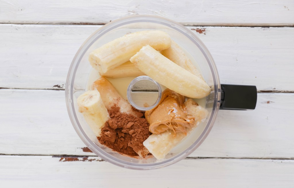 Food processor with ingredients for Chocolate Peanut Butter Ice Cream Cups; Vegan, dairy free and gluten free banana ice cream bites packed with cocoa and PB flavours.
