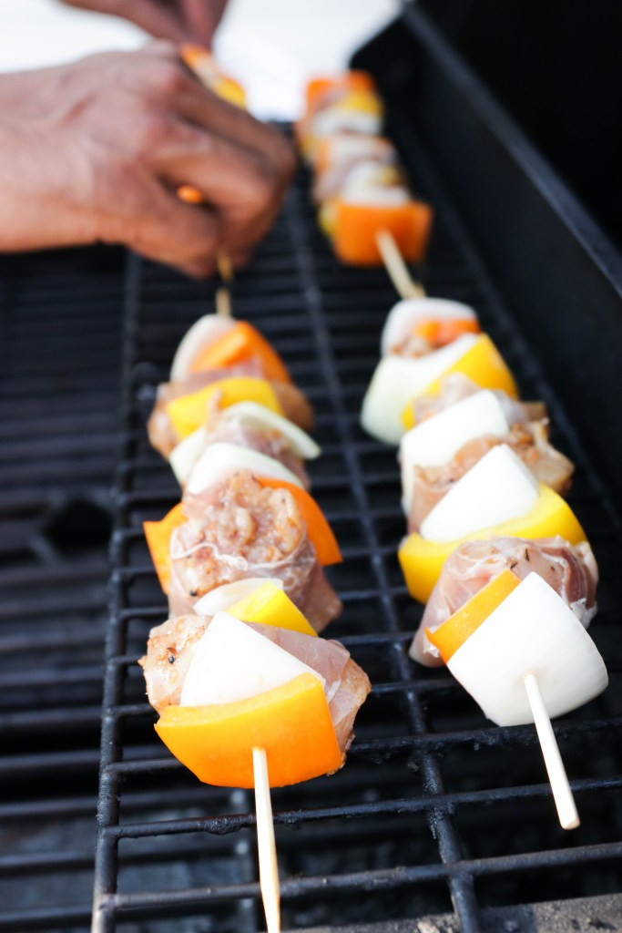 Adding skewers to the BBQ to be grilled