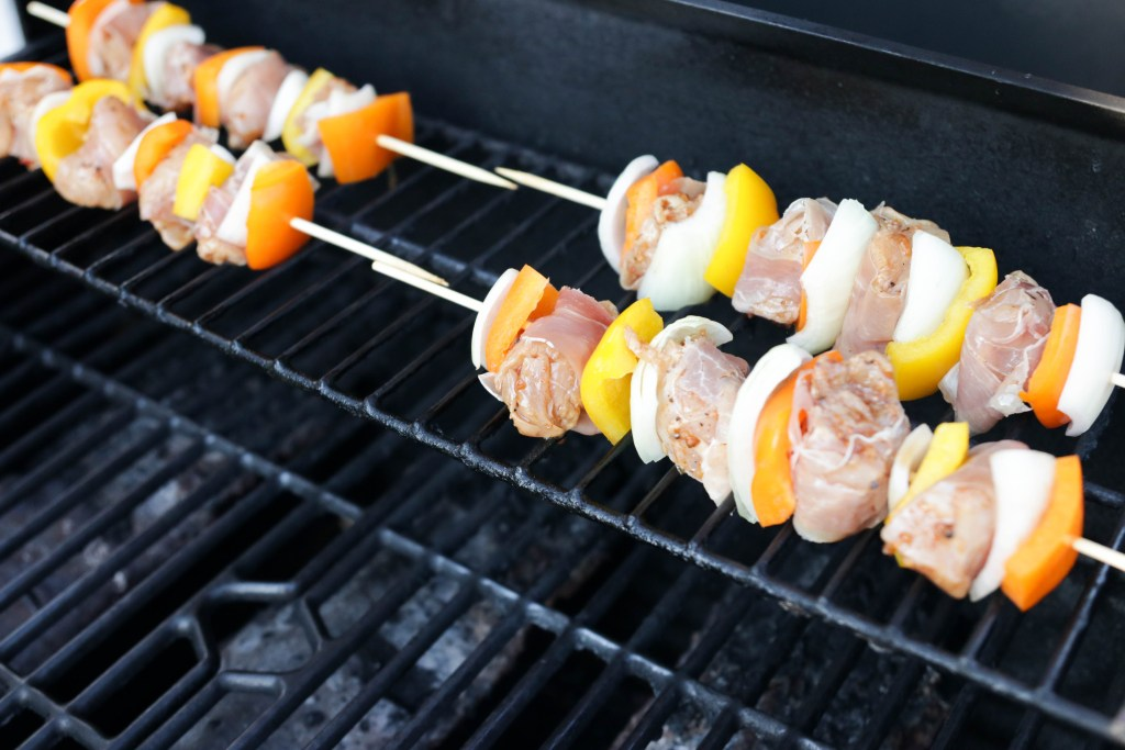 Grilling prosciutto wrapped chicken skewers on the BBQ