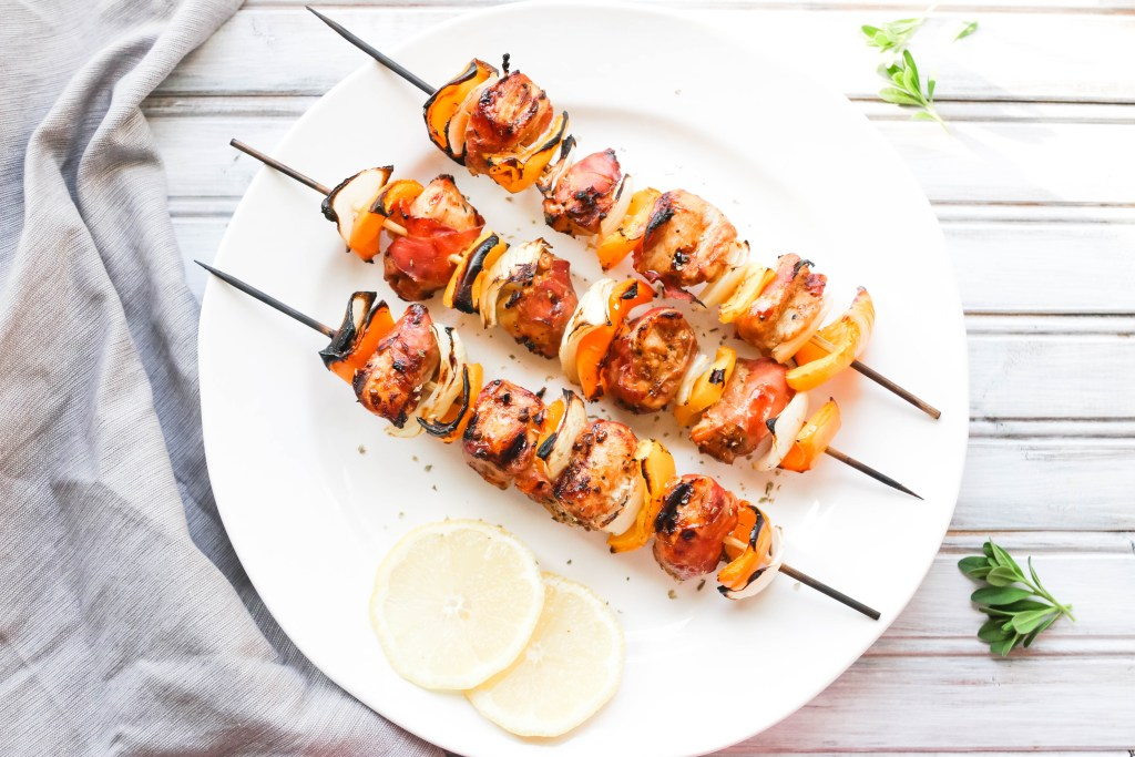 This Prosciutto Wrapped Chicken Skewers recipe is a quick and easy BBQ dinner that is bursting with salty goodness and juice peppers and onions. || Nikki's Plate