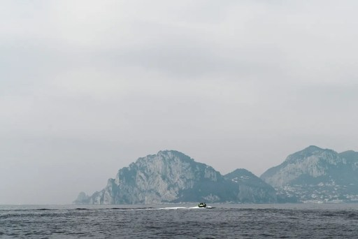 Capri through the fog, little boat in centre of image, cliffs in background. Very grey