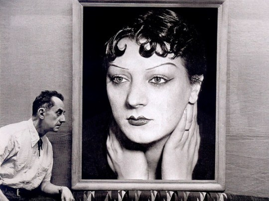 man-ray-in-front-of-a-portrait-of-kiki-de-montparnasse