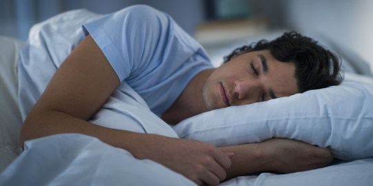 USA, New Jersey, Jersey City, Man sleeping in bed