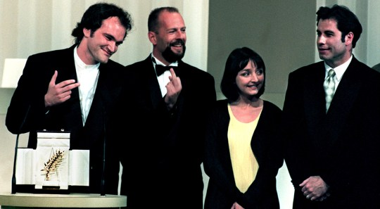 "American director Quentin Tarantino (L) makes an obscene gesture in reaction to a heckler after winning the Golden Palm for his film ""Pulp Fiction"", at the 47th Cannes Film Festival, May 23rd. Tarantino is seen with cast members from L to R: American actor Bruce Willis, French actress Maria de Medeiros, and actor John Travolta - RTXFCPM"