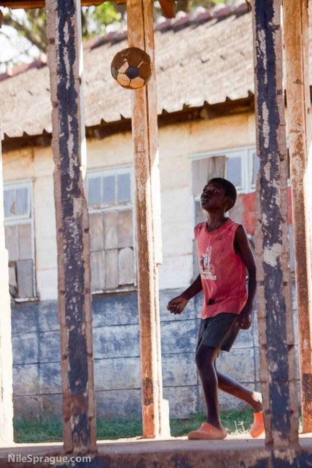 Boy playing with soccer ball, Mathare slum, Nairobi, Kenya.
