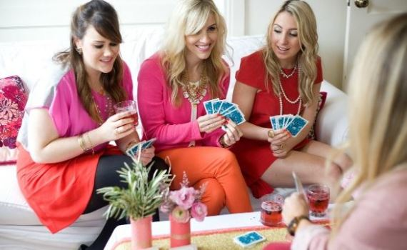 four women playing card games and having fun in a girls night in