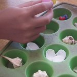 Filling the silicone soap mould with small seashells and lego figures