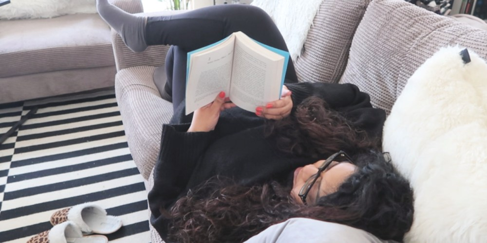 101 things to do in isolation, image of a woman lying on the sofa reading a book, nishi v