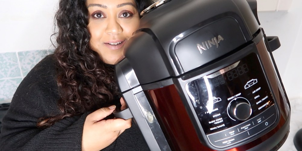 girl holding up a ninja foodi max multi cooker