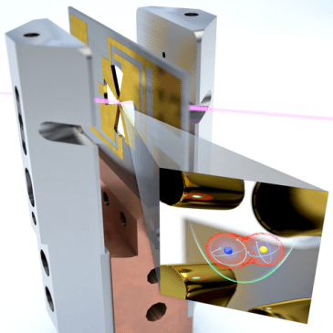 Computer-generated image showing a cross-shaped gold metal cutout on a red mount in between two metal posts, with an inset magnifying the cutout to show blue and yellow balls at the center.