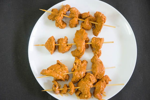 Bring the chicken to room temperature, and thread the 4 to 5 chicken pieces in each skewers. .