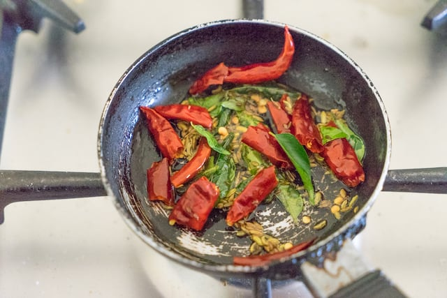 heat up a small pan, add oil , add the seasoning ingredients and let it splutter. Add the seasoning on green mutton curry.