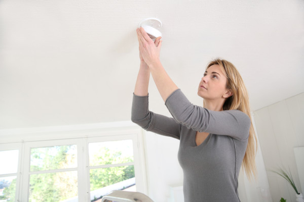 Woman Checking Smoke Detectors