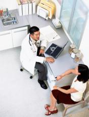 Photograph of a male doctor talking to a female patient
