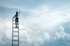 Blue cloudy sky with boy climbing ladder