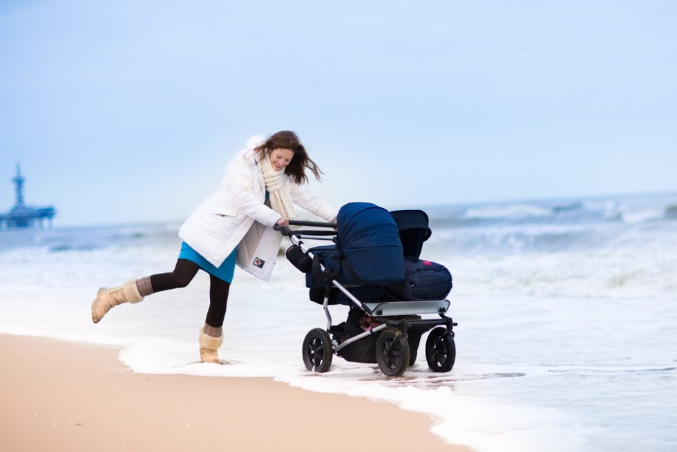 Mom walking with her baby in a stroller on beach