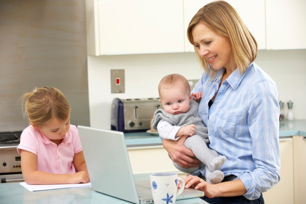 Multitasking mom working from home with children