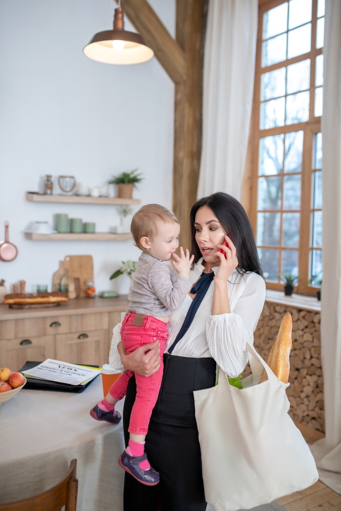 Multitasking mom with groceries, phone and child