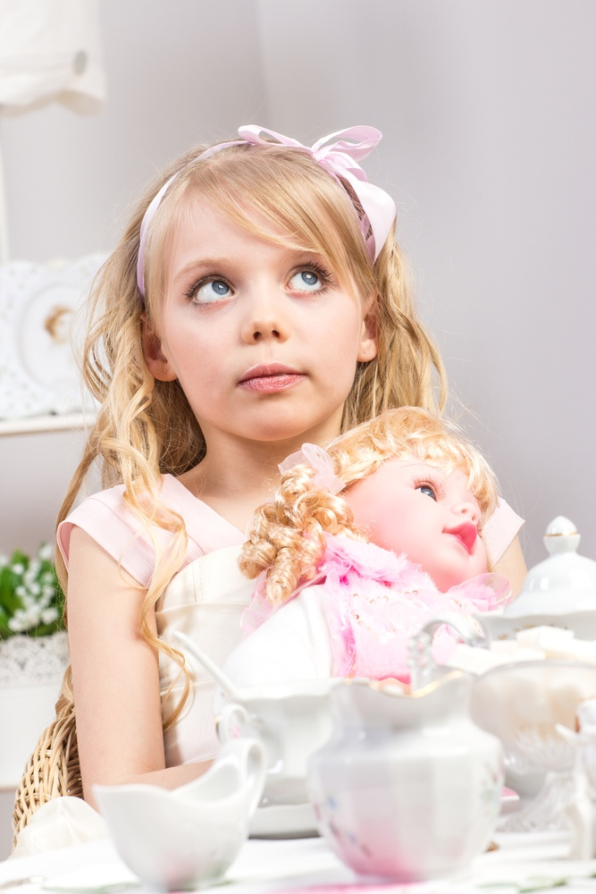 Little girl having tea party with doll