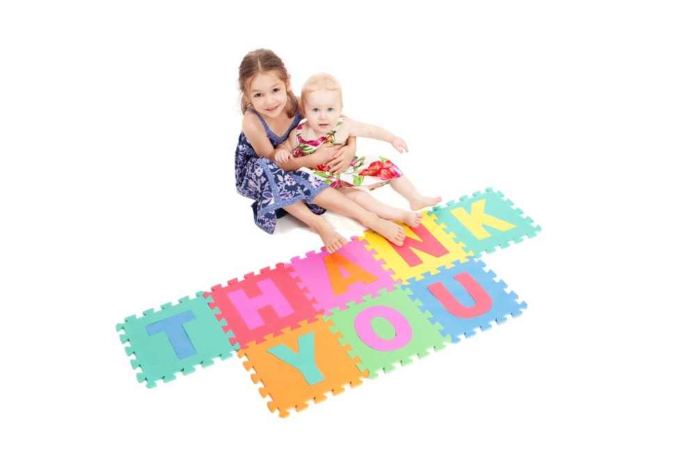 Girls spelling thank you with blocks.