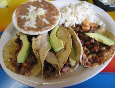 Four Tacos Al Patron: flour tortillas engorged with beef, bacon, peppers and more.