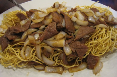 A gigantic platter of noodles, grilled beef and onion