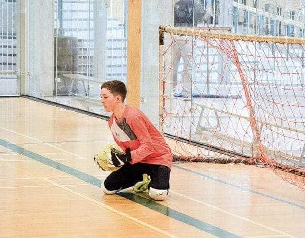 Mitchell Elliott of Range Lake North cradles the ball after making a stop during the Grade 7 boys final of Diavik Junior Super Soccer at St. Pat's Gymnasium on Sunday. - James McCarthy/NNSL photo