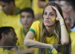 A fan of Brazil reacts during the semi-final football match between Brazil and Germany at The Mineirao Stadium in Belo Horizonte during the 2014 FIFA World Cup on July 8, 2014.  AFP PHOTO / PATRIK STOLLARZ