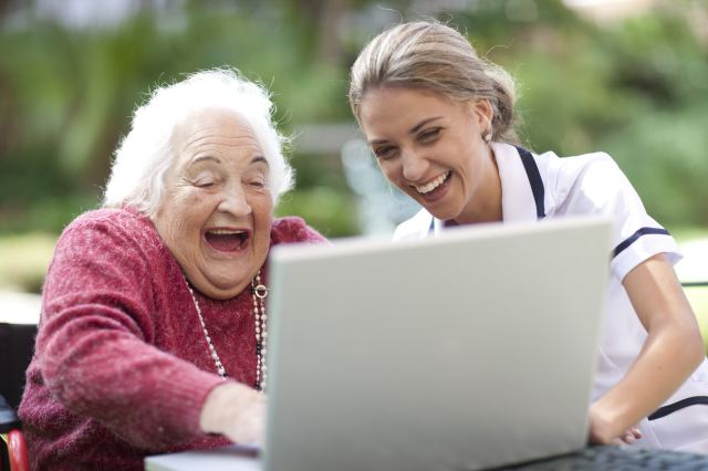 Happy caregiver and senior woman using laptop together