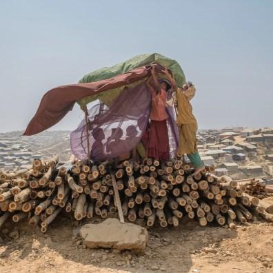 © Gabriele Cecconi. Campo profughi di Balukhali-Kutupalong, sottodistretto di Ukhia, Cox's Bazar, Bangladesh - Un gruppo di ragazzi si ripara dal vento e dalla sabbia in una tenda improvvisata nel campo di Balhukali. Con la deforestazione implementata per allestire i campi e costruire i rifugi, ora il suolo come la popolazione stessa rimangono direttamente esposti, con tutte le conseguenze del caso, alla forza degli agenti atmosferici.