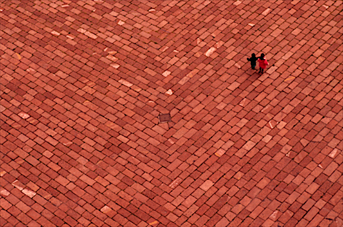 Arco della Pace – Per un caso fortuito fu possibile quel giorno a Milano salire in cima allo storico Monumento e da lassù io vidi quelle due mini/figurine sulla pavimentazione colore ruggine in basso. Una specialissima connotata da una rigorosa serialità. Ho atteso qualche istante perché i due mini/protagonisti non fossero al centro del fotogramma.