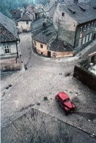*** Praga 1967 – di Franco Fontana – è il titolo di un'opera letteraria di Angelo M. Ripellino, studioso della letteratura slava. Andate in questa speciale città, dopo però aver letto questo libro. Questa fotografia non è allineata ai codici classici di Fontana. E, comunque, io ci ho percepito taluni umori di questa straordinaria città che non va raccontata, ma . Così è in questa immagine vista da Fontana nella periferia della città e lontana dalle suggestioni del turismo classico. In questa fotografia c'è il silenzio di un sobborgo dimenticato. E ciò a motivo della presa dall'alto che ci fa vedere l'insieme tutto con un solo segno di vita, l'automobile rossa che per contrasto cromatico rianima il sonnolento anonimato del luogo.