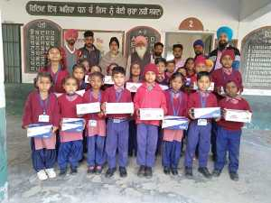 NRI team distributes uniforms and boots to needy students at Government Primary School Luhams