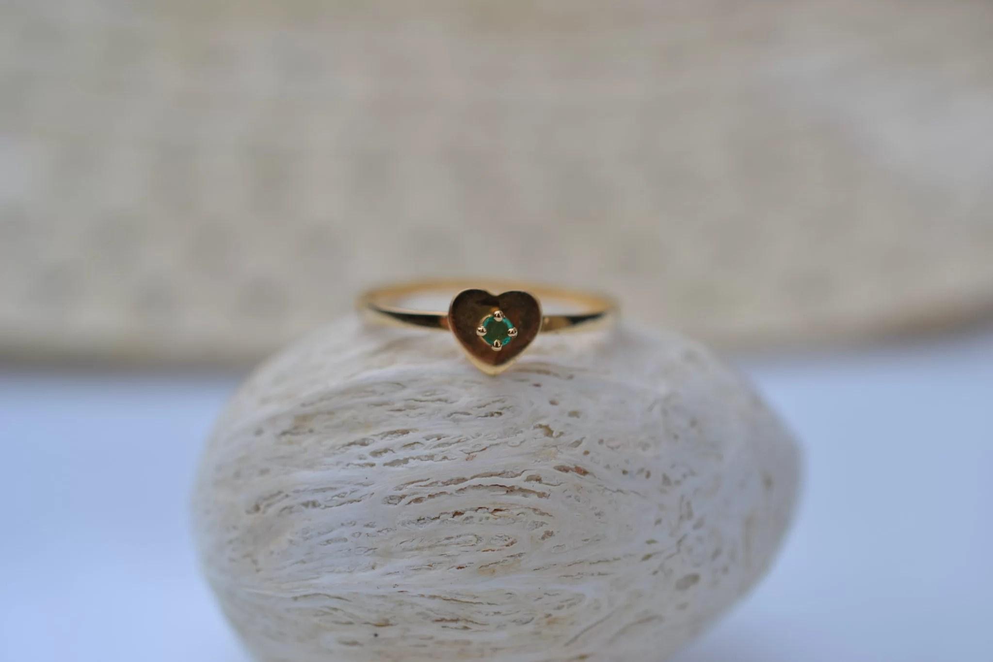Bague en Or jaune sertie d'une pierre verte sur une monture en forme de cœur bijou éthique
