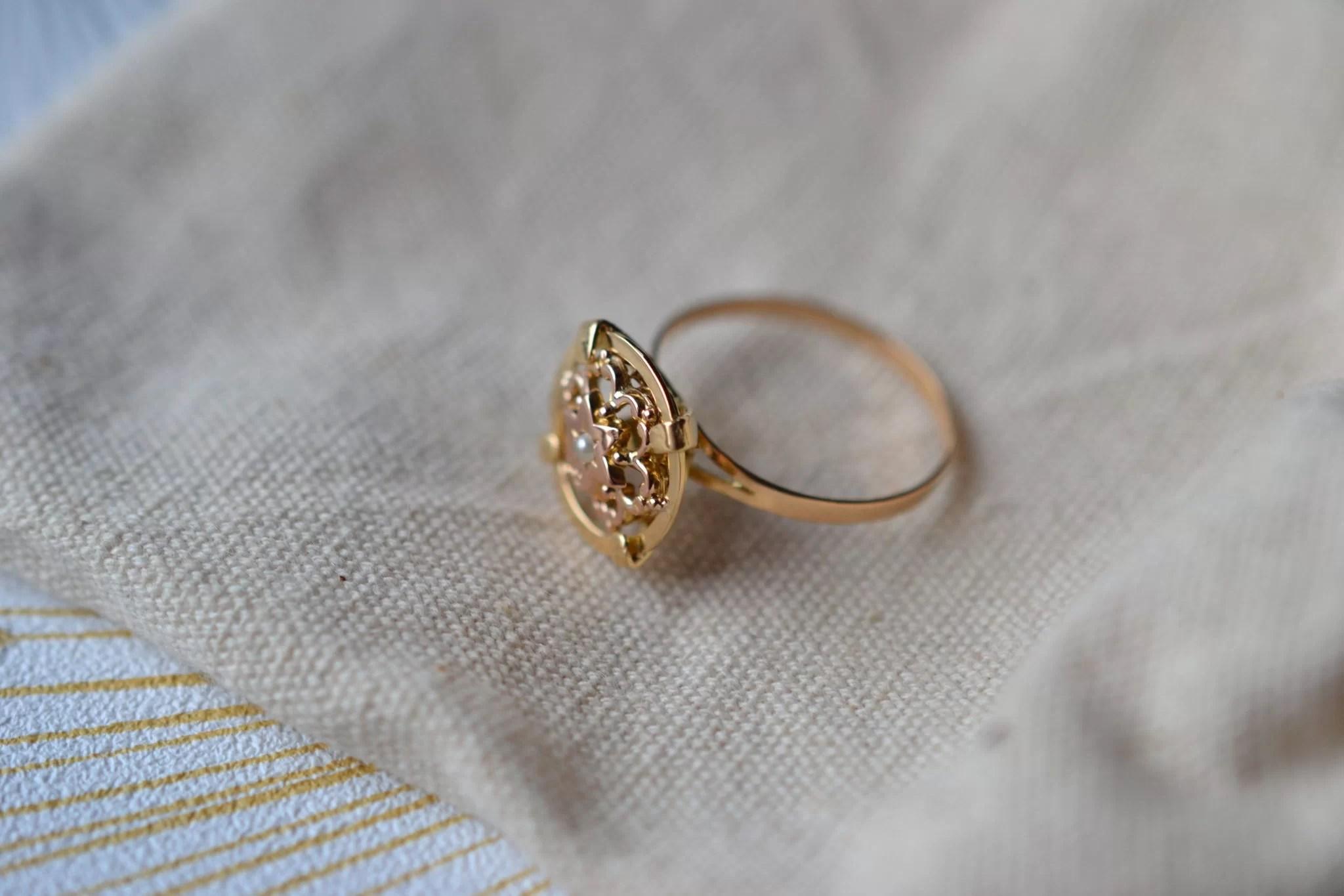 Bague en Or jaune ornée d_une demi-perle de culture sur un plateau en forme de disque, décoré d_un motif fleuri en Or rose - bague de seconde main