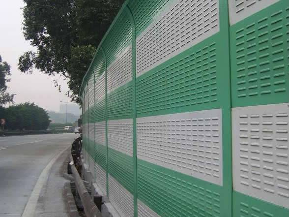 Green and white aluminum sound barrier along a heavy freeway.