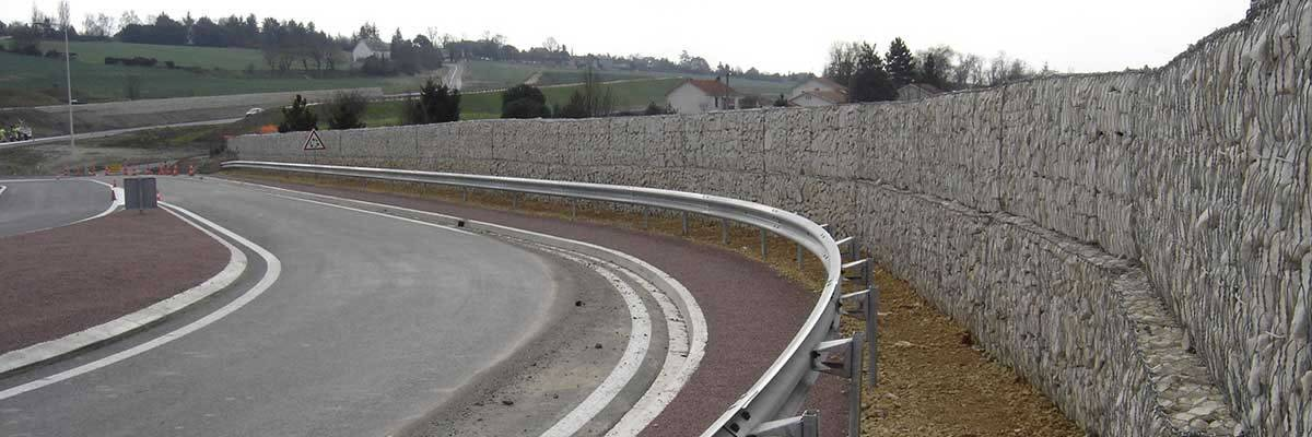 Thick gabion sound wall along a busy highway.