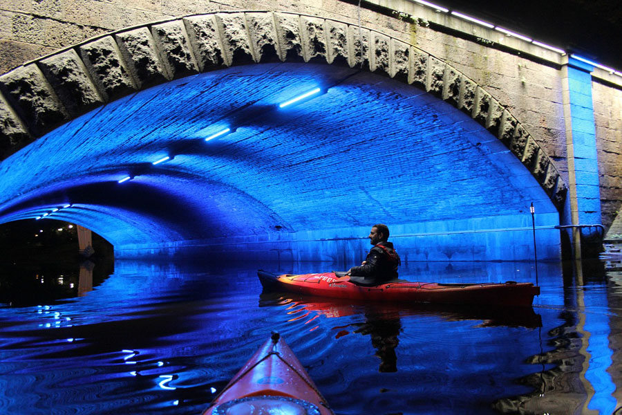 Nighttime kayaking tour under a bridge