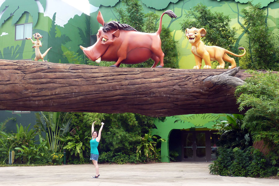 Woman posing with gigantic statues of Simba, Pumbaa, and Timon at Disney's Art of Animation