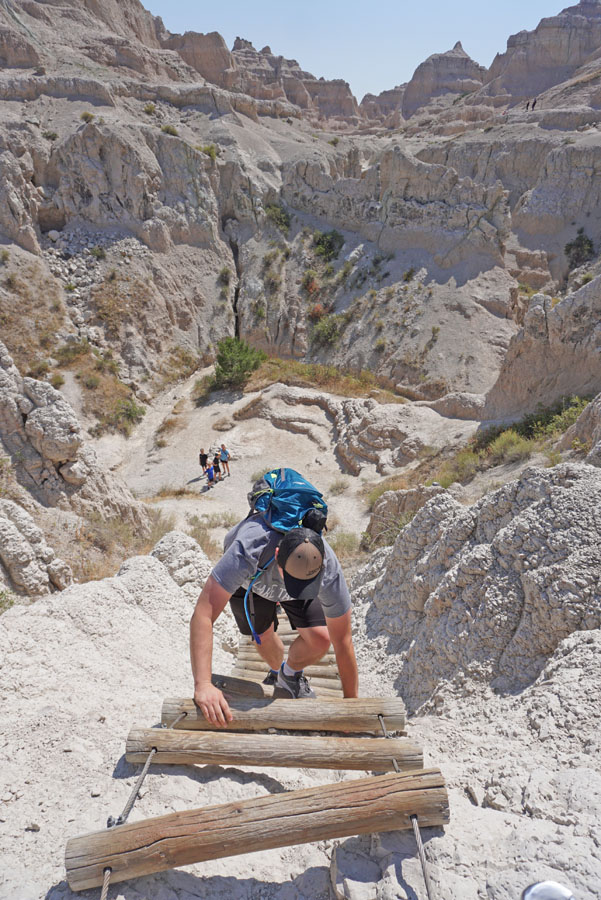 Man climbing a ladder along the Notch Trail, one of the best hiking trails in Badlands National Park
