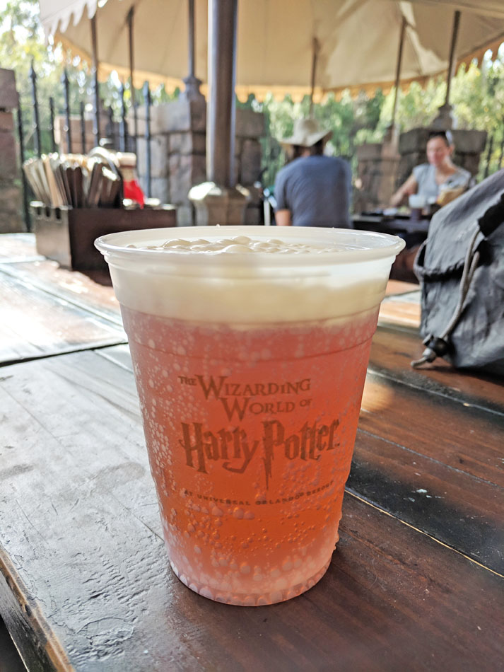 Cup of foamy butterbeer at the Three Broomsticks
