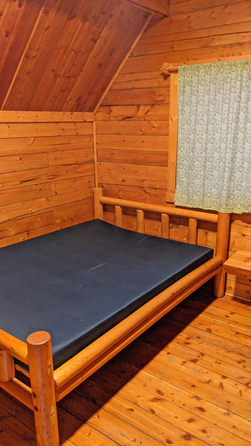 Bed inside the rustic cabin at the KOA Devils Tower