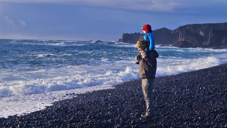 Man and child on Djupalonssandur beach in Iceland