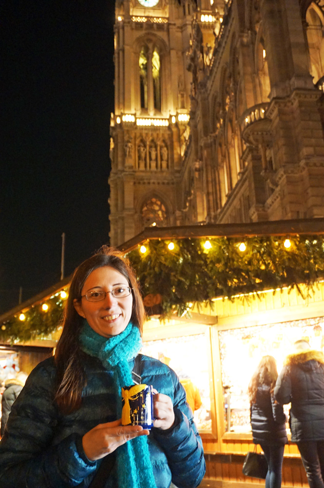 Woman holding a blue mug of gluhwein in front of the Vienna Rathaus