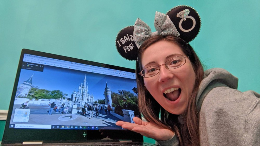 Woman wearing Minnie ears posing in front of a Google Street View image of Cinderella Castle