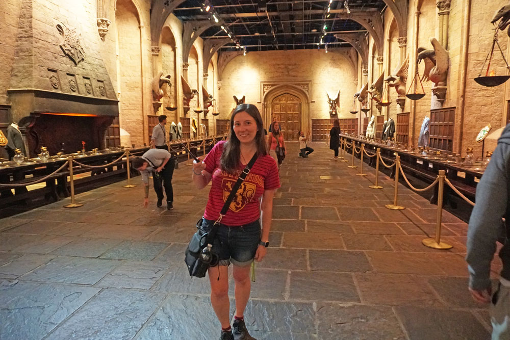 Woman posing with a wand in the Great Hall at the Harry Potter Studio Tour London