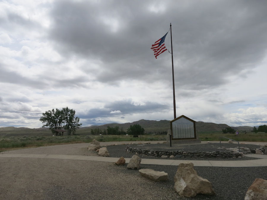 Cloudy skies over walkways and a monument at Heart Mountain Interpretive Center